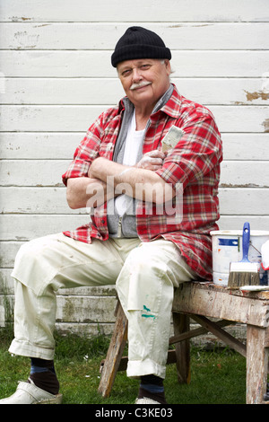 Elderly man painting his summer cottage, Sweden. - Stock Photo