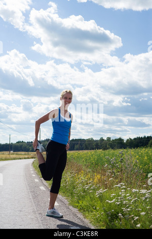 A woman doing stretching exercises, Sweden. - Stock Photo