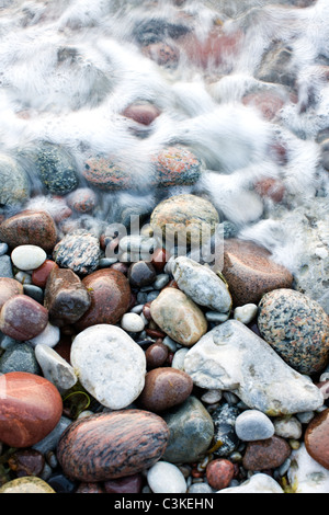 Waves sweeping over pebbles on beach - Stock Photo