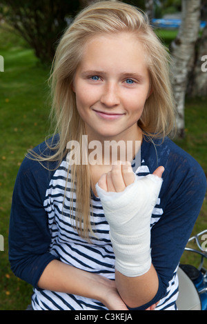 Teenage girl with bandage on hand, smiling, portrait - Stock Photo