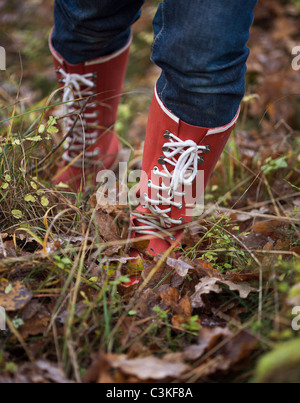 Legs of mid adult woman wearing rubber boots standing in grass - Stock Photo