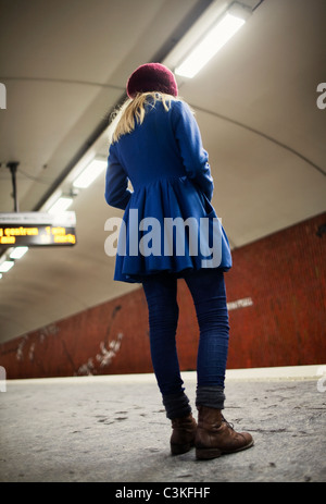 Teenage girl (14-15)standing on underground station platform - Stock Photo