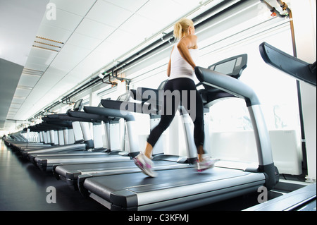 Woman exercising on treadmill in gym - Stock Photo