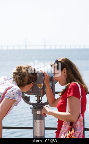 Two women admiring the Oresund bridge, Skane, Sweden. - Stock Photo