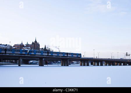 Passenger train passing through bridge over frozen lake - Stock Photo