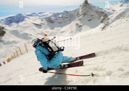 A skier carves a turn on piste in the ski resort of Courchevel in France - Stock Photo