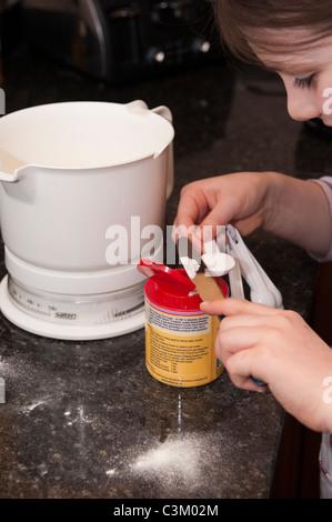 A young girl baking, measuring baking powder on a spoon. - Stock Photo