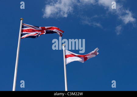 Two flags flying in the wind: one Union Flag and one English Flag - Stock Photo