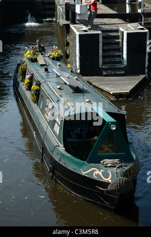 Flower-covered narrow boat, navigates out of Camden Lock (Hampstead Road Lock), moving towards Hawley Lock on the - Stock Photo