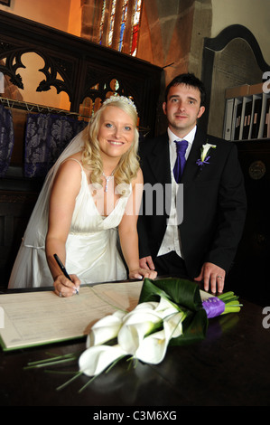 A couple sign the marriage registers during the ceremony at their wedding - Stock Photo