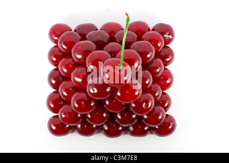 Sour cherries ordered in form of a pyramid top view isolated on white - Stock Photo