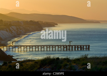 Golden sunrise light over coastal hills, pier, and beach at Gaviota Beach State Park, near Santa Barbara, California - Stock Photo