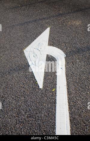A turn left arrow marking the road. - Stock Photo