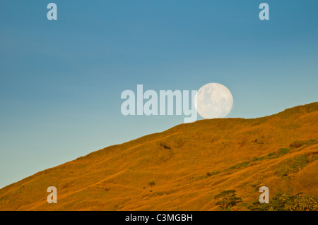 Full moon rising over the Mountains of  Yawasa Islands, Fiji - Stock Photo