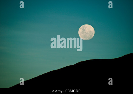 Full moon rising over the Mountains of the Yawasa Islands, Fiji - Stock Photo