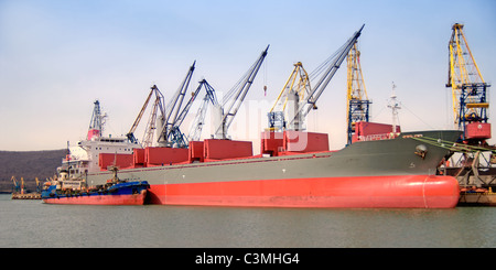 A cargo ship is being loaded with coal - Stock Photo
