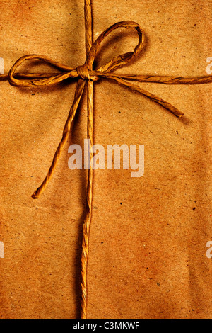 Rope ribbon tied on old brown paper background - Stock Photo