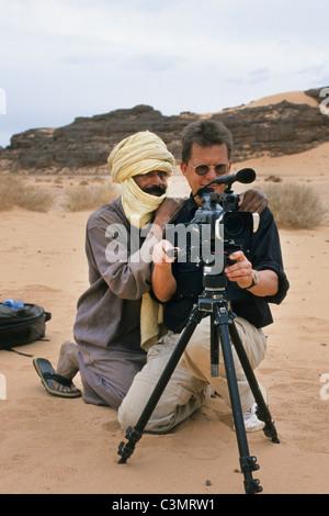 Algeria, Djanet, Sahara Desert, Photographer Frans Lemmens looking at film with Touareg man. - Stock Photo