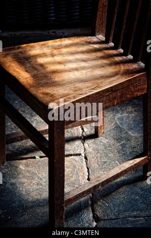 Old oak wooden kitchen chair on a welsh slate floor - Stock Photo