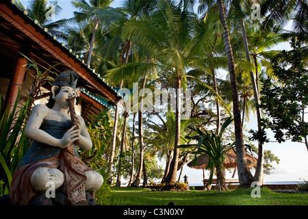 Indonesia, Island Bali, near Tejakula village, Gaia Oasis Resort. Statue in front of bungalow. - Stock Photo