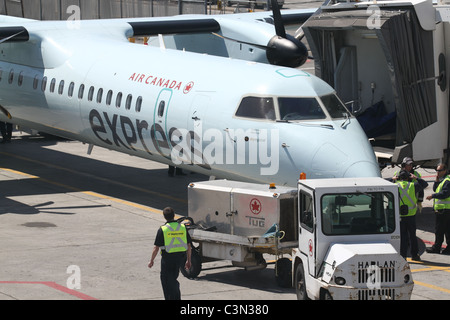 Air Canada workers prepping a plane for take-off - Stock Photo