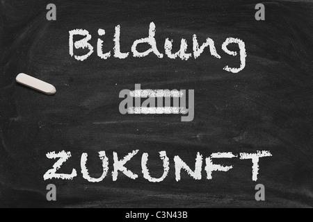High resolution black chalkboard image with German letters Bildung equals Zukunft. - Stock Photo