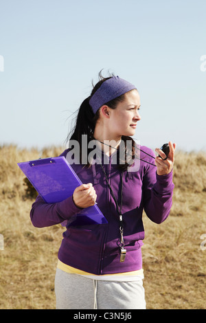 Woman holding clipboard and stopwatch - Stock Photo