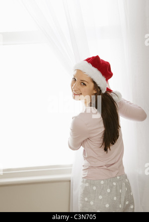 Woman pulling curtains aside, laughing - Stock Photo