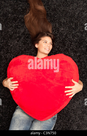Woman lying with a big heart in her arms - Stock Photo