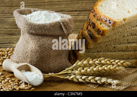 Fresh homemade bread and flour in small burlap bag - Stock Photo