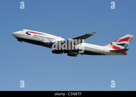 Long haul international air travel. British Airways Boeing 747-400 jet plane flying in the sky and climbing on departure - Stock Photo