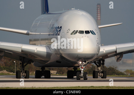 Lufthansa Airbus A380 long-haul passenger jet lining up for departure from Malta. Closeup front view emphasizing - Stock Photo
