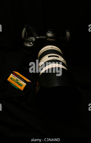 Camera. Canon film SLR model, on black, with box of film. - Stock Photo