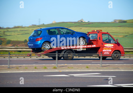 Broken down car on a flatbed truck - Stock Photo