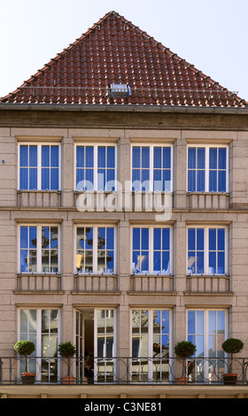Old house with windows reflecting beautiful blue sky in city of Munster in North Rhine-Westphalia, Germany - Stock Photo