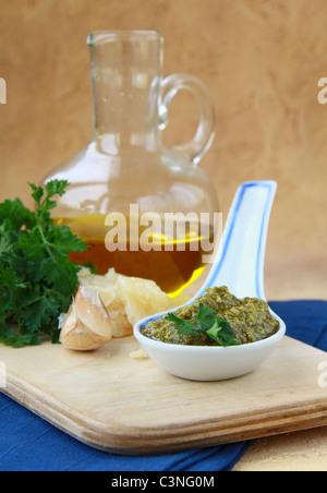 Basil pesto in a ceramic spoon - Stock Photo
