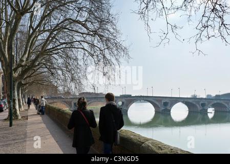 Young couple walking along banks of River Garonne near 16thC Pont Neuf bridge, Toulouse, Haute Garonne, Midi Pyrenees, - Stock Photo