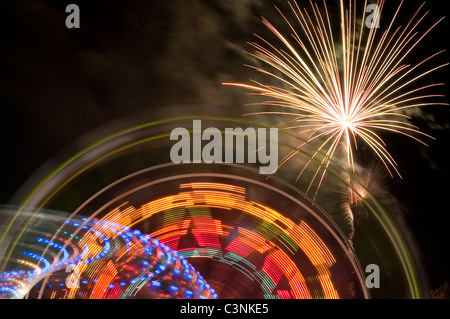 Evergreen State Fair ferris wheel at night with rides and motion with fireworks Snohomish County Monroe Washington - Stock Photo