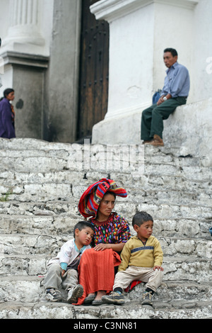 A woman and her children sit on the steps of Iglesia de Santo Tomas. Chichicastenango, Quiche, Guatemala, Central - Stock Photo