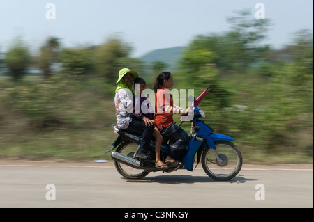 Three people on a motor cycle in North East Thailand. - Stock Photo