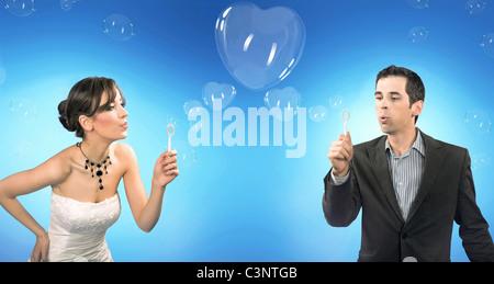 Wedding couple blowing heart shaped romantic soap bubbles - Stock Photo