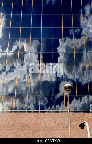 clouds in deep blue sky reflected in windows of tall building - Stock Photo