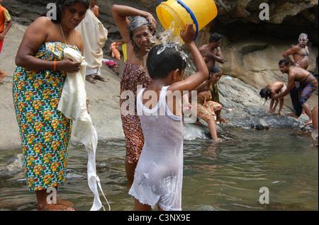 A girl washing at Rawana Ella Falls (Ravana). - Stock Photo