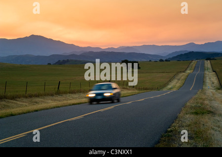 Golden sunrise light over long straight two lane country road and rolling hills in Spring, Santa Ynez Valley, California - Stock Photo