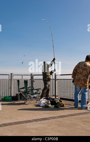 A fisherman casts off the pier at Southwold , Suffolk , England , Britain , Uk - Stock Photo