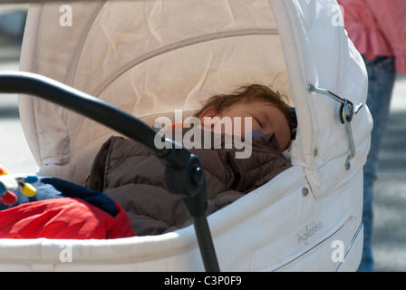 Baby sleeping in baby carriage - Stock Photo