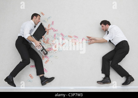Two businessmen, one of them holding money case, side view, portrait, elevated view - Stock Photo