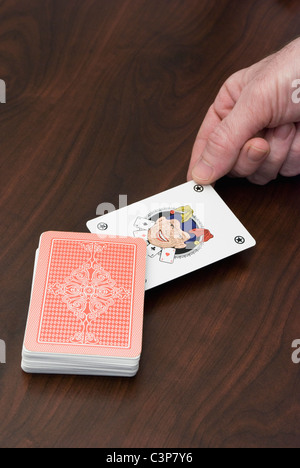 picking up a joker card - Stock Photo