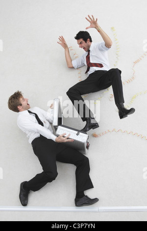 Two businessmen, one holding suitcase, the other scaring him, elevated view - Stock Photo
