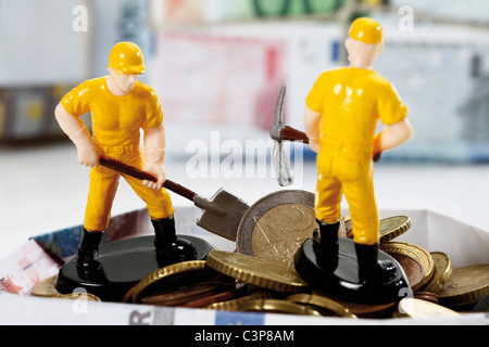 Figurine workers standing on pile of euro coins holding shovel and hammer - Stock Photo